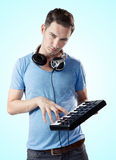 Deejay with headphones pressing keys on midi keyboard Stock Photo