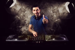 Deejay mixing at party. Deejay smiling to camera while showing ok sign. He is illuminated by two vintage spot light reflectors Stock Photo