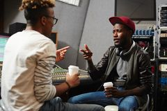 Deejay and musician. Young rapper explaining deejay which type of sound recording he wants to be produced Royalty Free Stock Photos