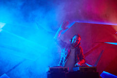Deejay in night club. Ecstatic deejay standing by turntables with raised hand Stock Images
