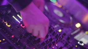 Deejay tweaking controls on sound board, party in the nightclub. Stock footage stock video
