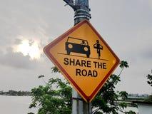 Deel de weg; Gele verkeersteken met auto en fietsersymbolen, pictogrammen stock afbeeldingen