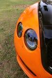 Deel oranje auto op asfaltachtergrond Oranje luxeauto stock afbeeldingen