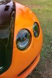 Deel oranje auto op asfaltachtergrond tuning Oranje luxeauto stock afbeelding