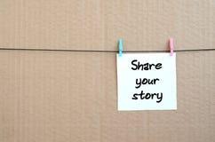 Deel uw verhaal De nota wordt geschreven op een witte sticker die hangt royalty-vrije stock afbeeldingen