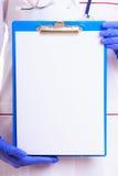 Deel vrouwelijk lichaam in laboratoriumlaag Artsenverpleegster met leeg klembord Stock Afbeeldingen