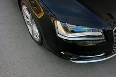Deel zwarte auto op asfaltachtergrond tuning Oranje luxeauto stock afbeeldingen