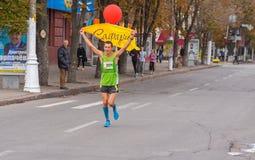 : Deelnemer als hartstimulator met rode ballon die gewenste tijd op een de Marathon` ras van ` Dniepr Eco toont Stock Foto
