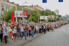 Deelnemers van Onsterfelijk Regiment met portretten van hun verwanten die langs de straat op Overwinningsdag lopen in Volgograd stock foto's