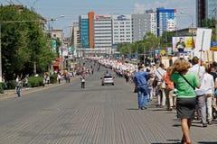 Deelnemers van Onsterfelijk Regiment met portretten van hun verwanten die langs de straat op Overwinningsdag lopen in Volgograd stock afbeelding
