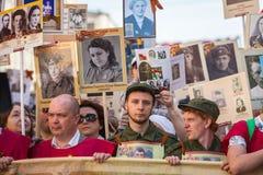 Deelnemers van Onsterfelijk Regiment - openbare actie, waarin de deelnemers banners/portretten droegen stock afbeeldingen