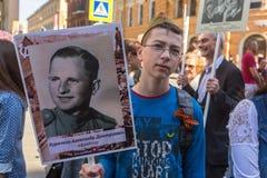 Deelnemers van Onsterfelijk Regiment - openbare actie, waarin de deelnemers banners/portretten droegen stock fotografie