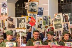 Deelnemers van Onsterfelijk Regiment - openbare actie, waarin de deelnemers banners/portretten droegen stock foto