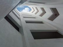 Deep atrium gray building overlooking the blue sky Stock Image