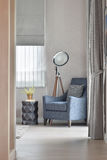 Deep blue armchair with stylish standing lamp in the corner of living room at home stock photo
