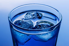 Deep blue colored drink with ice on abstract blue background. Deep blue colored drink with ice close up. On abstract blue background Royalty Free Stock Image