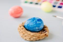 Deep blue easter egg on nest over bright background. Stock Photo