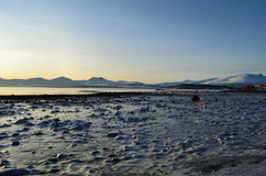 Deep blue ice on sea shore with fjord and snowy mountain. Background Stock Images