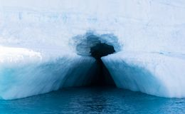 Deep Blue Keyhole in the Iceberg. A deep turquoise blue keyhole entrance into an iceberg in the lighter turquoise blue Southern Ocean surrounding the Antarctic Stock Image