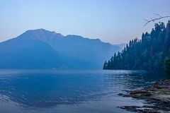 Deep blue lake at dusk in summer with mountain royalty free stock photo