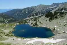 Deep blue lakes and gray rock summit during the sunny day with clear blue sky Stock Photo