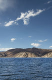 Deep blue mountain lake and desert hills stock images