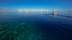 Deep blue ocean and boat Stock Images