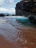Red sand beach. Deep blue ocean next to red sand beach colors stock photography