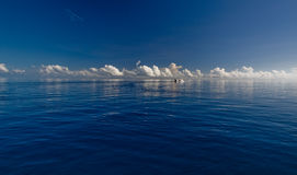 Deep blue ocean and white clouds. Deep blue ocean and reflecting white clouds on the horizon Royalty Free Stock Photo