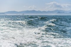 A deep blue sea with island in distance with medium water wave ripple. royalty free stock photo