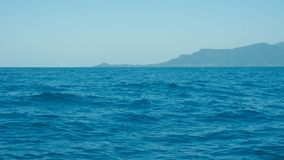 A deep blue sea with island in distance with medium water wave ripple stock images