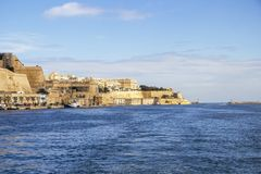 Seaside view to Quarry Wharf and Valletta, the two lighthouses of Grand Harbor in the distance. Deep blue seaside view to Quarry Wharf and Valletta, the two Royalty Free Stock Image
