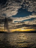 Unique circular cloud pattern over the harbour of Geneva, Switzerland. Deep blue sky exposed by circular cloud pattern above the famous Jet d`Eau fountain stock image