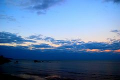 Deep blue cloudy sky over the sea. Deep blue sky with low clouds over the sea with some rocks after sunset in winter stock images