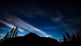 Deep Blue Sky Over Mountain. A vibrantly blue, starry night sky stretches over a mountain top Stock Photos