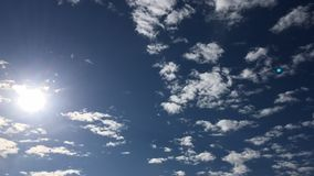 Deep blue sunny sky with white clouds. Blue sky with cloud close-up. White fluffy clouds in the blue sky. copy space for text or i. Deep blue sunny sky with stock video footage