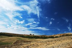Deep blue and white. Sky over cultivated land in center italy royalty free stock image