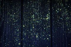 On the deep blue wood background glow yellow and green stars. Christmas stock image
