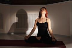 Deep breath. Redhead taking deep breath while meditating in a dark gym Stock Photo