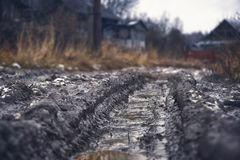Car rut on russian dirt road. Deep car rut on russian dirt road in winter thaw royalty free stock image