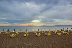 Deep Cloudy Blue Sunset Sky with Yellow Lights above Water and Many Folded Chaise-Lounges Umbrellas Beach stock photo