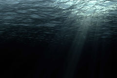 Deep dark ocean waves from underwater background. Light rays shining through royalty free stock photo