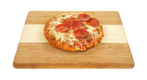 Deep dish personal size pizza. A freshly cooked personal size thick pan pizza on a wood cutting board royalty free stock images