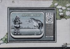 Wall art mural in Deep Ellum, Dallas, Texas. Pictured is a wall art mural featuring a battle between a dinosaur and a robot.  It was painted by Frank Campagna Stock Photo