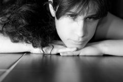 Deep Expression. A sad looking young woman facing the camera on a tile floor Stock Photos