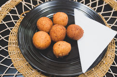 Deep fried balls made from green banana sitting on black plate, traditional latin american food, classy table setting Royalty Free Stock Images