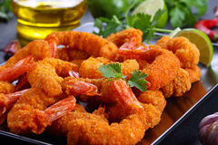 Deep fried breaded shrimps on plate. Delicious deep fried breaded shrimps served with lime wedges and coriander leaves on black plate on slate tray with garlic Stock Image