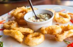 Deep fried calamari rings with sauce bowl Stock Images