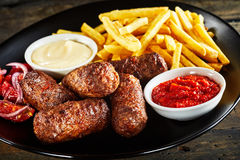 Deep fried cevapcici meat patties and potato chips royalty free stock image