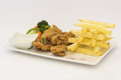 Deep-Fried Chicken (chicharrón de pollo), Fried chicken nuggets, French fries and vegetables with chili sauce Stock Images